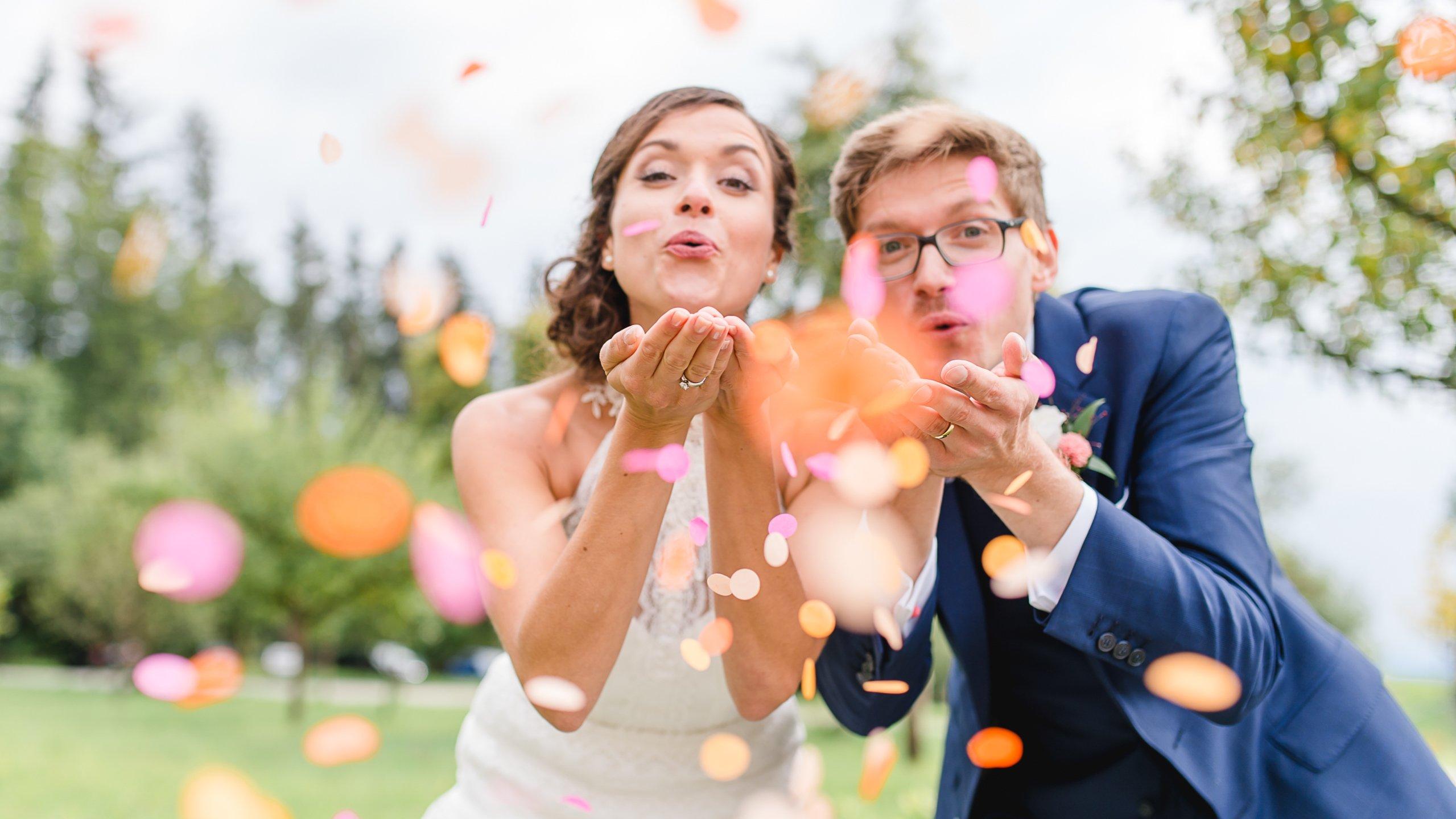 Brautpaar pustet Konfetti in die Kamera, Hochzeitsfoto auf Gut Sonnenhausen bei München