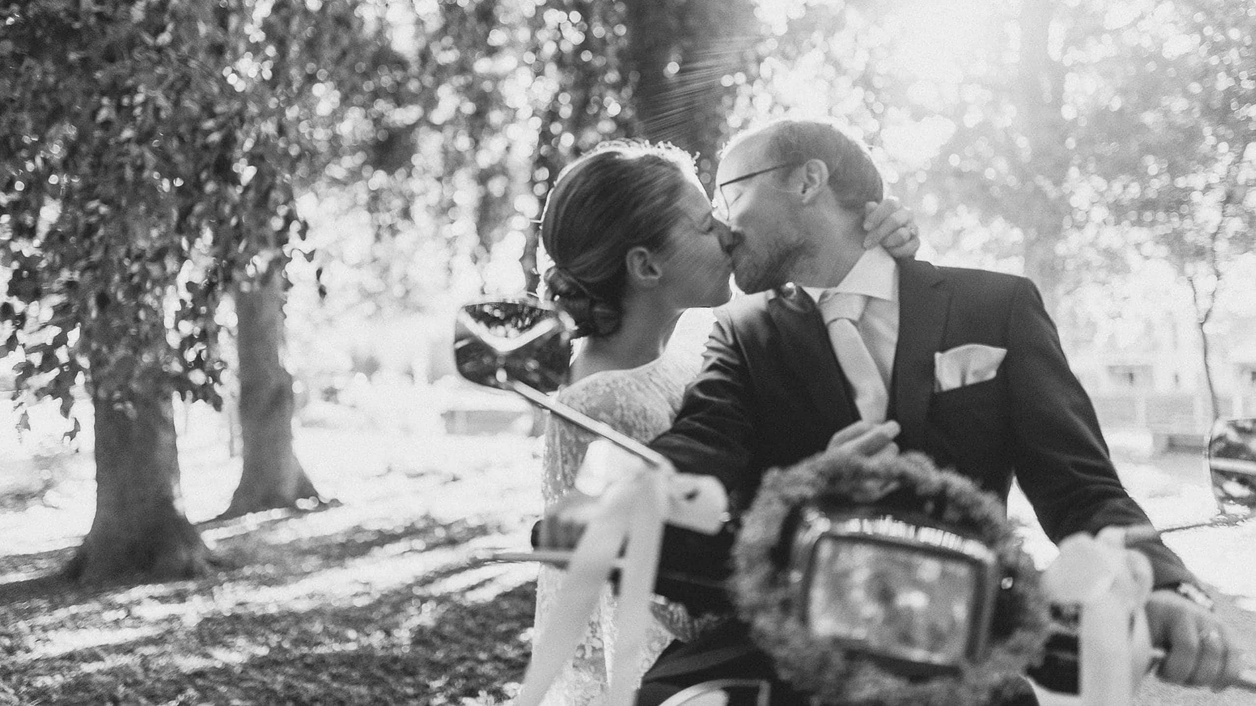Hochzeitspaar, küssend auf Vespa und Gegenlicht in Schwarz-Weiß