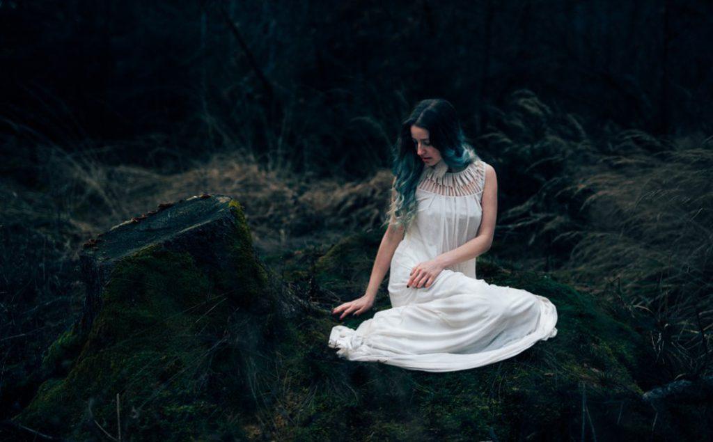 Portraitfoto von Mädchen im Wald, blaue Haare, sitzend im Moos, in München