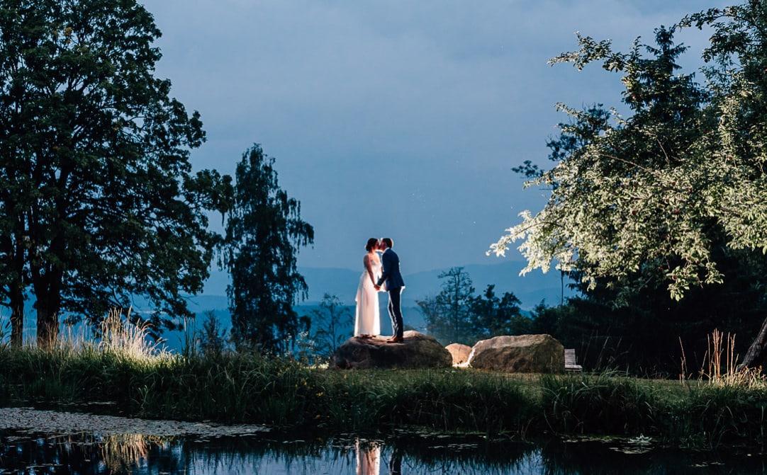 Jung und Wild design: Hochzeitsfotografie im Bayerischen Wald bei Bodenmais: Brautpaar am Weiher in der blauen Stunde mit Gegenlicht