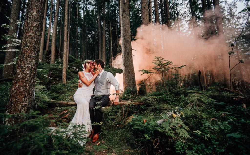 Jung und Wild design: Hochzeitsfotos von Traumhochzeit mit Rollstuhl am Eibsee unterhalb der Zugspitze, Brautpaar küssend im Wald mit orangener Rauchbombe