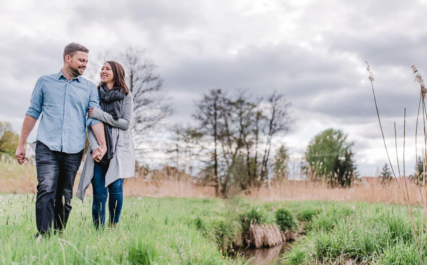 Engagementshooting auf dem Land, Pärchenfotos im Wald, Paarfotos bei Wolken und Wind, Paarfotos von Jung und Wild design bei und um München